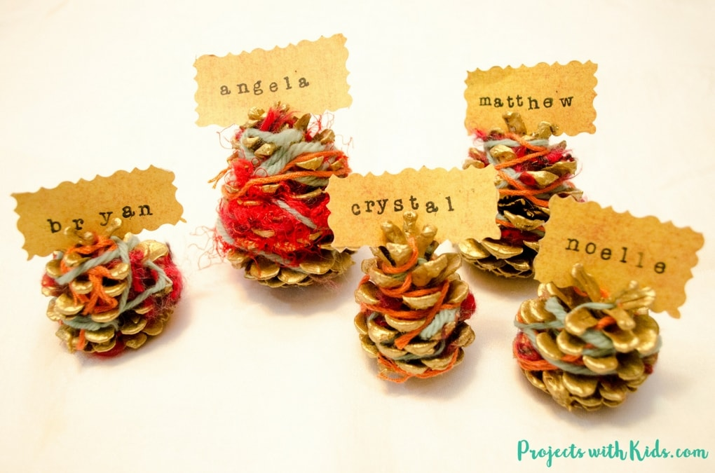 Bring some natural elements to your holiday decor this year with these beautiful pinecone place card holders. This is a simple craft that kids of all ages will be able to do and will have fun making! A perfect decoration for your holiday table that can be used year after year.