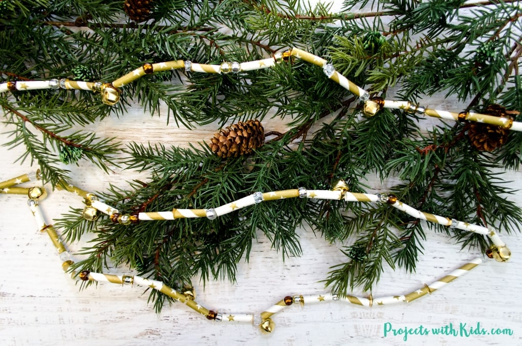 This Christmas garland with paper straws is sparkly and shimmery and would be a gorgeous addition to any Christmas tree or mantle! This is a simple and easy Christmas craft to make, perfect for preschool aged kids (and beyond!) and makes a great fine motor skills holiday activity.