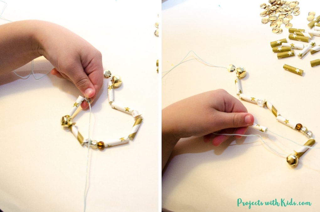 This Christmas garland with paper straws is sparkly and shimmery and would be a gorgeous addition to any Christmas tree or mantle! This is a simple and easy Christmas craft to make, perfect for preschool aged kids (and beyond!) and makes a great fine motor skills holiday activity. #christmascraft #kidmadechristmas #kidscraft #projectswithkids