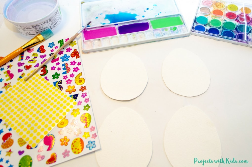 Use stickers to create this gorgeous watercolor easter egg art with kids. Easy watercolor techniques that produce amazing results. So simple and fun for kids of all ages! Free printable easter egg template included.
