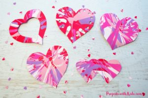 Spin painting hearts make the perfect Valentine's Day art project for kids. Kids will have a blast spinning their hearts and making cool patterns. An easy project for preschool kids to make on their own and an awesome process art project for kids of all ages!