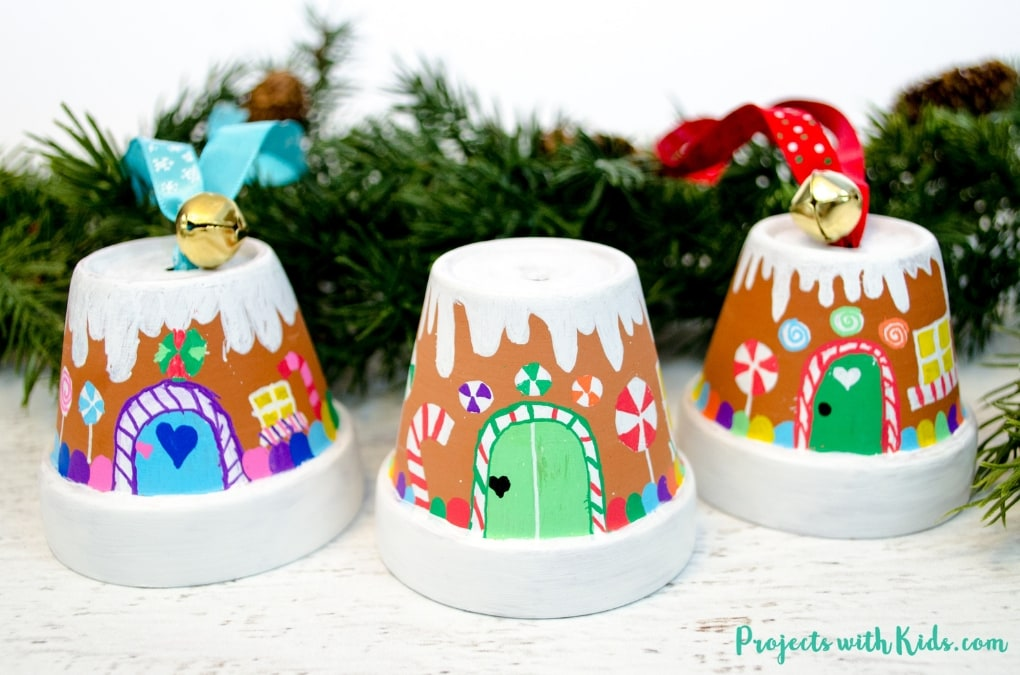 Transform mini terra cotta pots into the sweetest gingerbread house ornaments! Kids will love making this adorable Christmas craft to hang on the tree or give as a special gift.