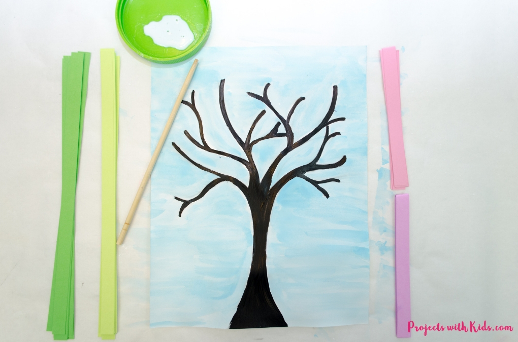 Make this gorgeous blossom spring tree craft with kids! Use easy paper quilling techniques and a free printable tree template.