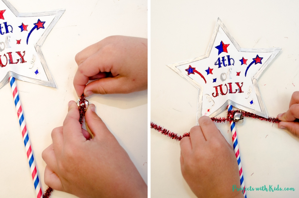 Putting on a bell and pipe cleaner onto a paper straw to finish making a 4th of July wand.