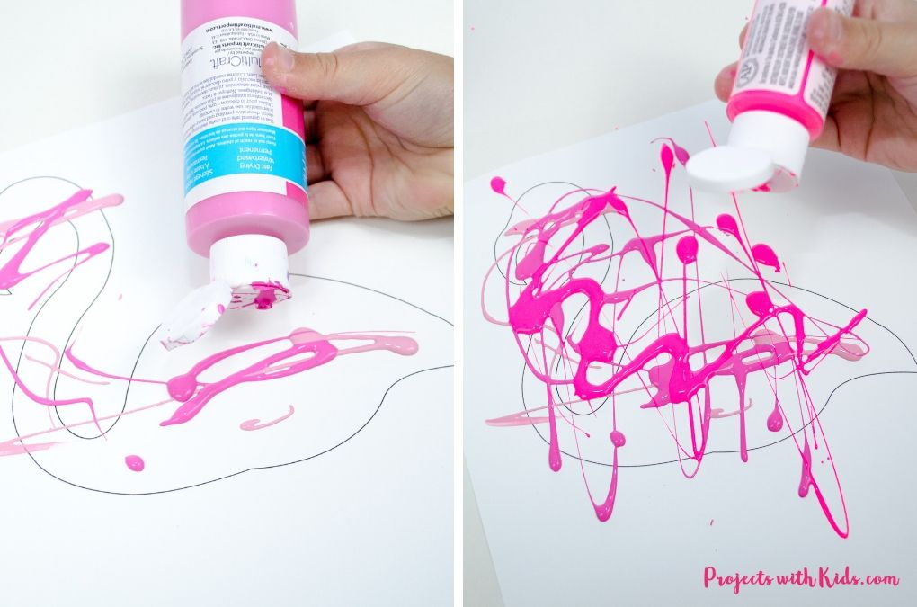 Squeezing out pink paint onto white paper.