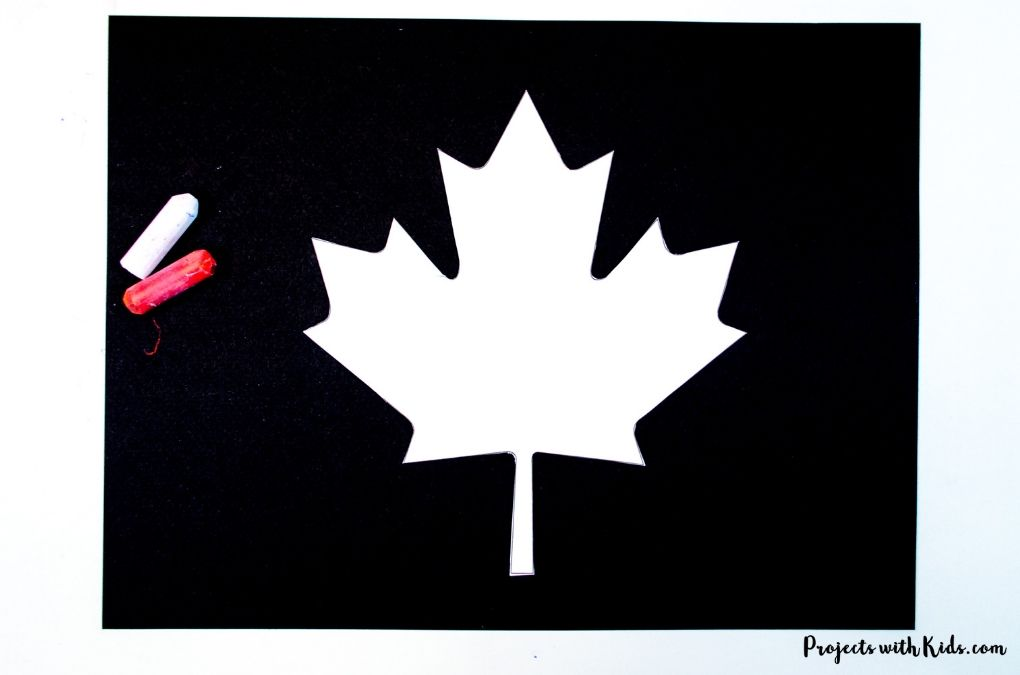 White maple leaf cut out on black paper.