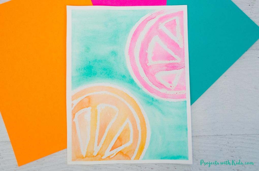 Watercolor painting of an orange slice and grapefruit slice on a green background.