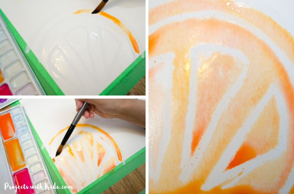 Painting with orange watercolor paint over white oil pastel to make a resist image of an orange fruit slice.