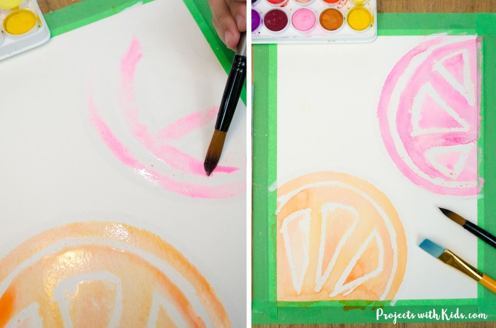 Painting with pink watercolor paint on paper to make a grapefruit slice.