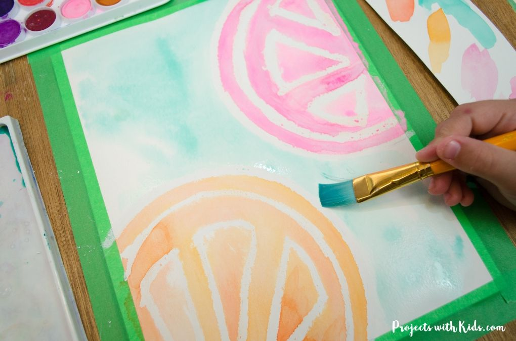 Painting green watercolor paint onto paper to finish a watercolor resist citrus painting.
