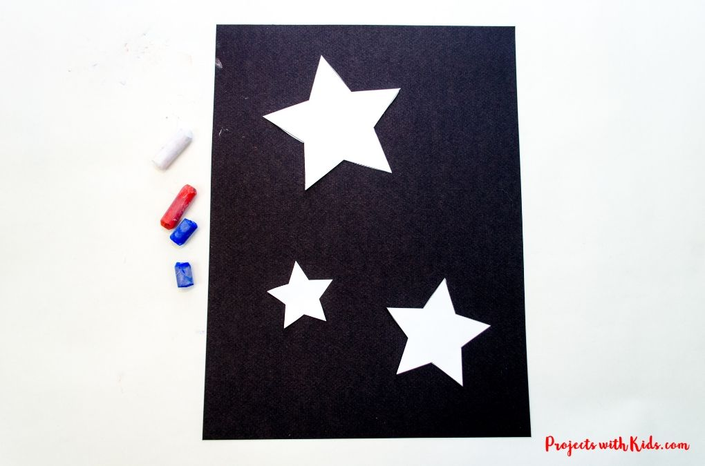 White stars cut out and placed onto black pastel paper.