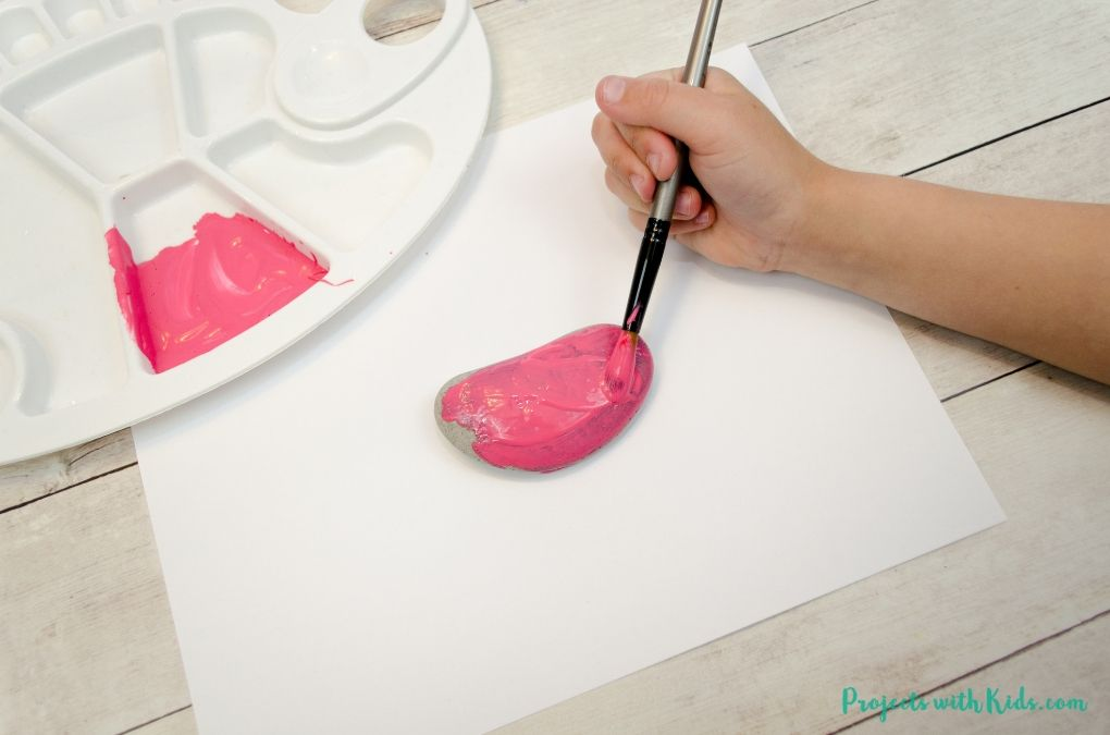 Painting a pink color onto a rock.