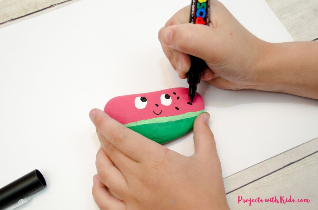 Drawing on watermelon seeds to a painted rock with a black paint pen.