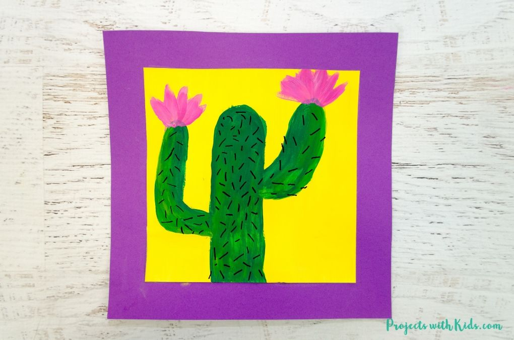 Cactus painting with pink flowers on a yellow painted background glued to purple paper.