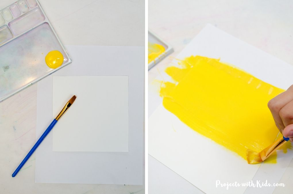 Painting yellow paint onto white paper.