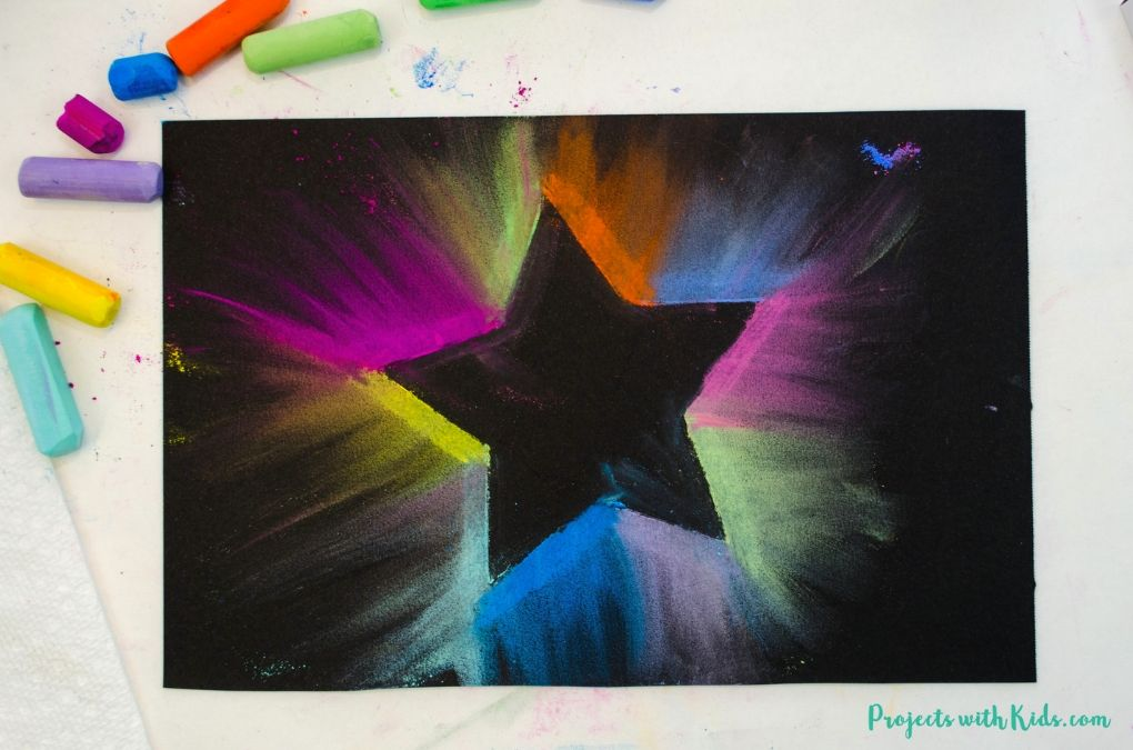 Finished image of a colorful chalk pastel star drawing on black paper.