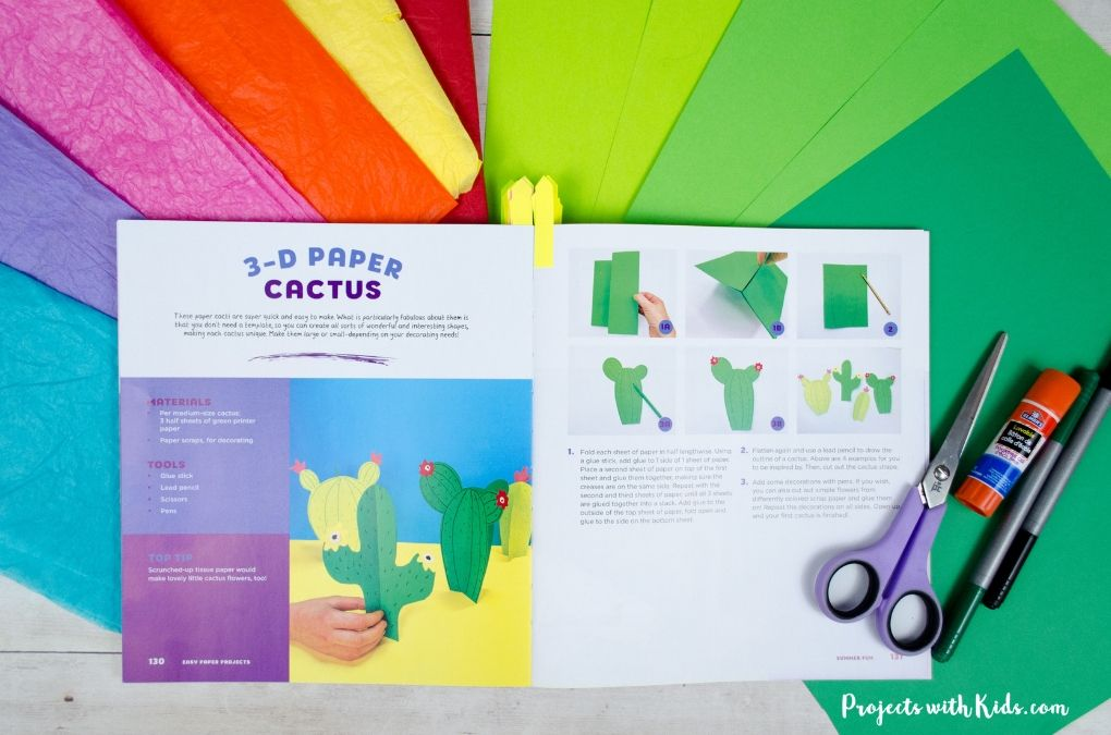 Easy paper projects book open to the cactus craft page lying on top of colorful paper.