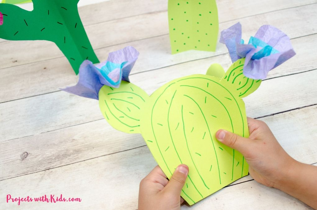 Hand holding a paper cactus with blue tissue paper flowers.