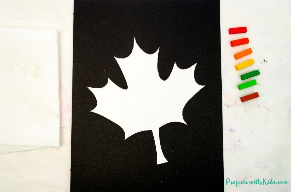 Maple leaf cut out and taped onto black drawing paper, fall chalk pastel colors