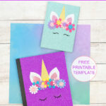 2 unicorn notebook covers made with sparkly paper and felt flowers