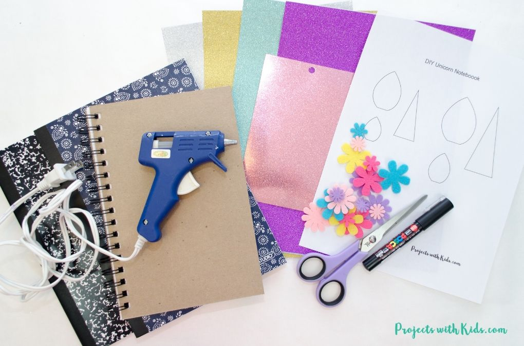 Supplies needed to make a unicorn notebook cover: notebook, glitter paper, felt flowers, glue gun, printable, scissors, paint pen