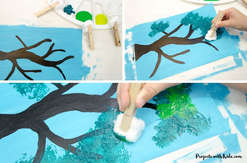 Using a cotton ball attached to a clothespin to paint green leaves onto a blue sky and black branch.