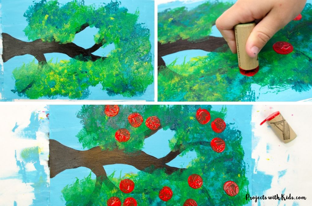 Painting apples on a tree using a cork and red paint.