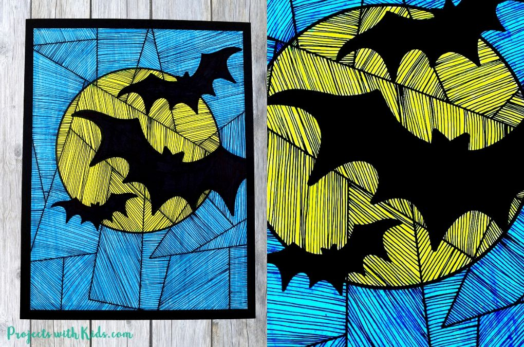 Finished bat art project with 3 bats, a full moon and blue background.