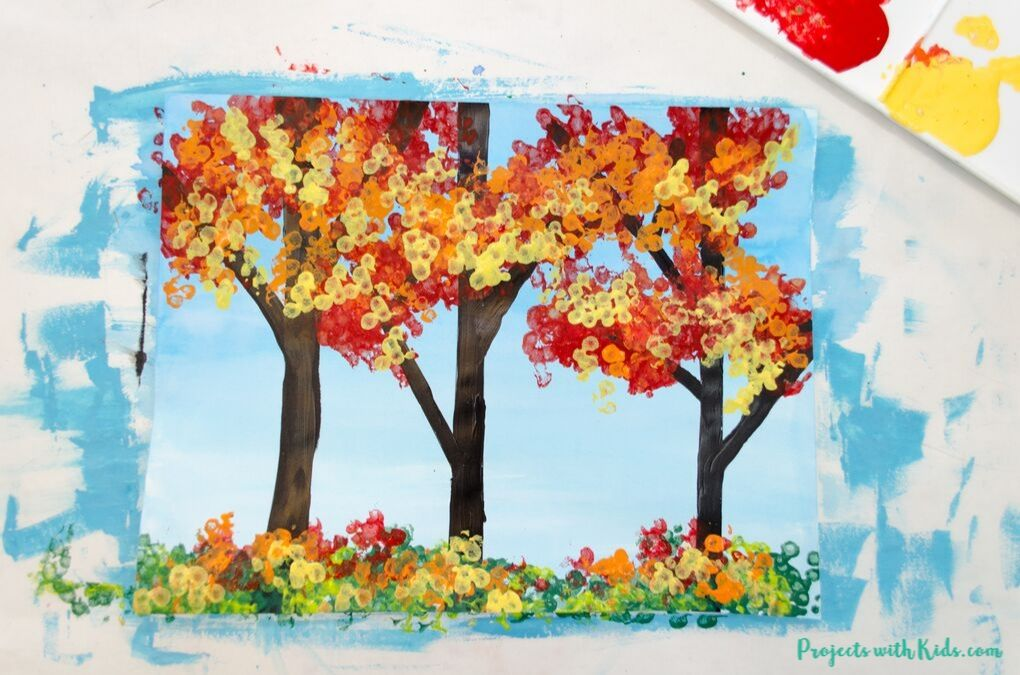 Finished image of a fall forest painting using bundled q-tips to paint the leaves.