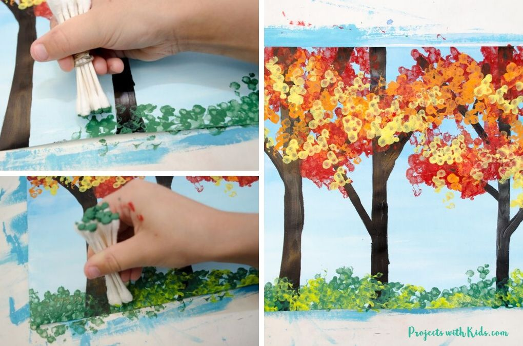 Using bundled q-tips to paint green grass on a fall tree painting for kids