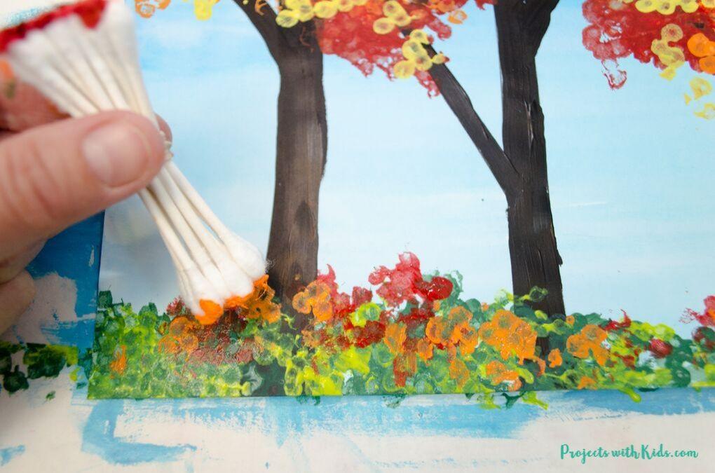 Painting fallen leaves with bundled q-tips on a fall forest craft for kids