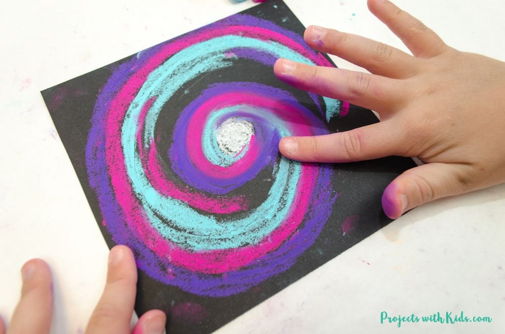 Blending chalk pastel colors on black paper for galaxy art