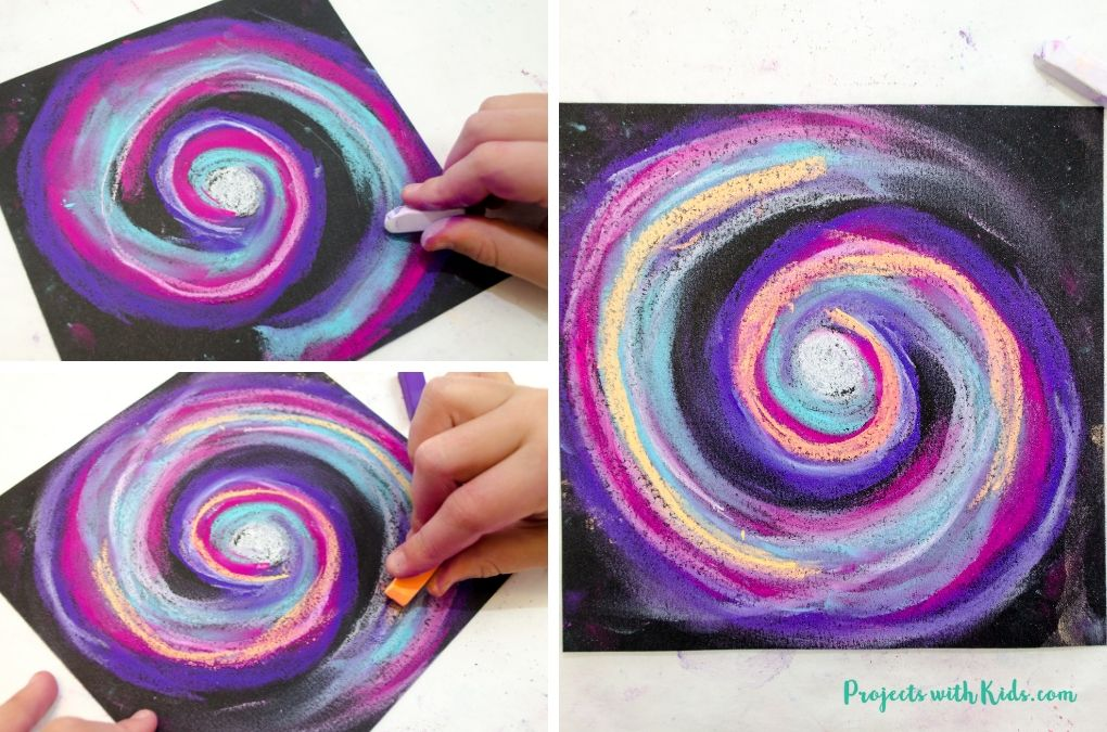 Adding white and orange chalk pastel colors to galaxy art for kids