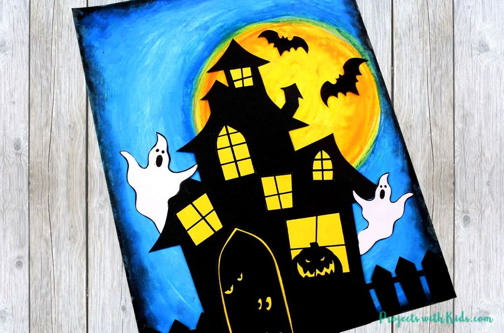 Paper haunted house, ghost and fence glued onto a blue and orange background.