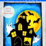 Halloween art project with a full moon and blue sky drawn with oil pastels, paper haunted house and ghosts.