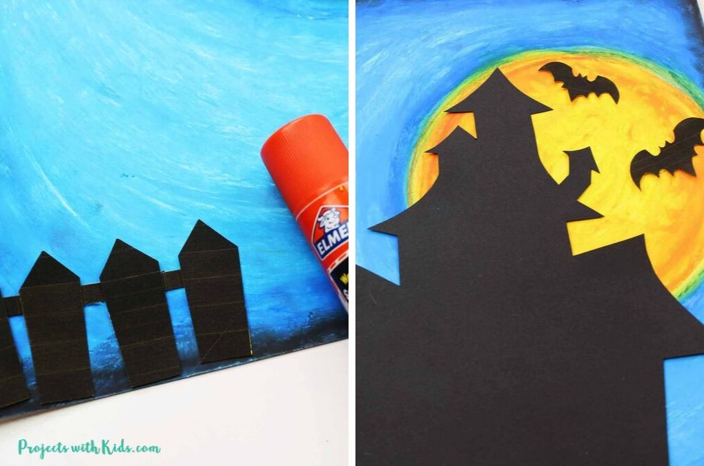 Glueing down a black fence, haunted house and bats cut of out black paper onto a blue and orange oil pastel background.