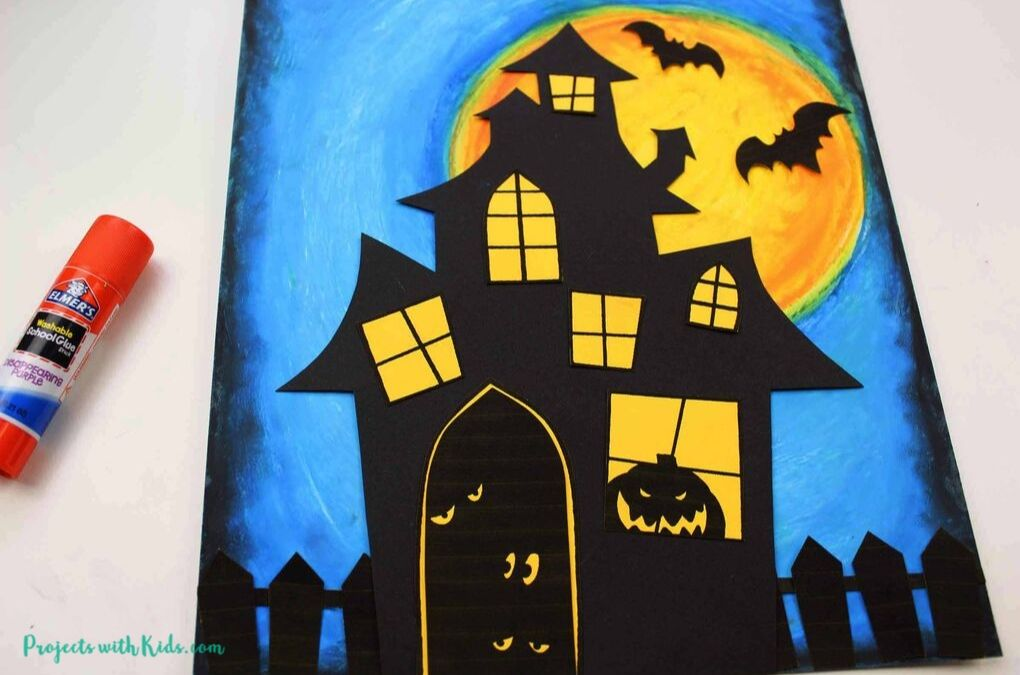 Haunted house craft made with paper and oil pastels.