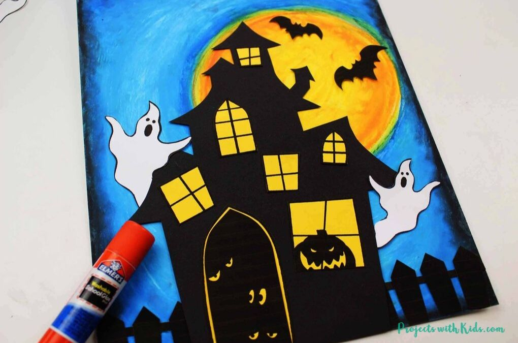 Adding in white paper ghosts to a haunted house art project.