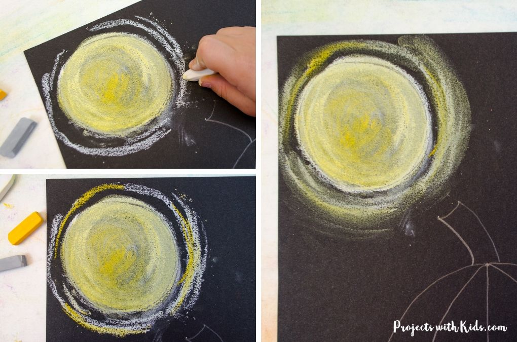 Finishing drawing in a full moon with chalk pastels.