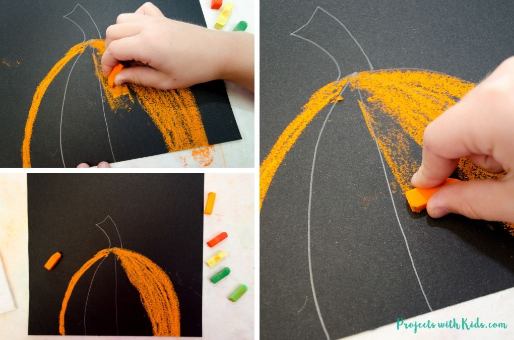 Coloring in a pumpkin on black paper with orange chalk pastel.
