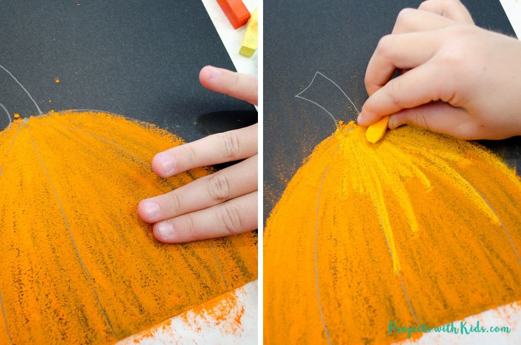 Using fingers to smudge orange chalk pastel and adding light orange to a pumpkin art project.