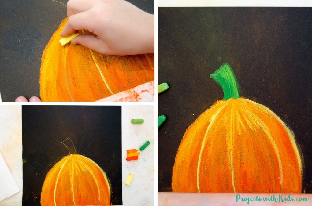 Adding in yellow detail with a chalk pastel to a pumpkin art project.
