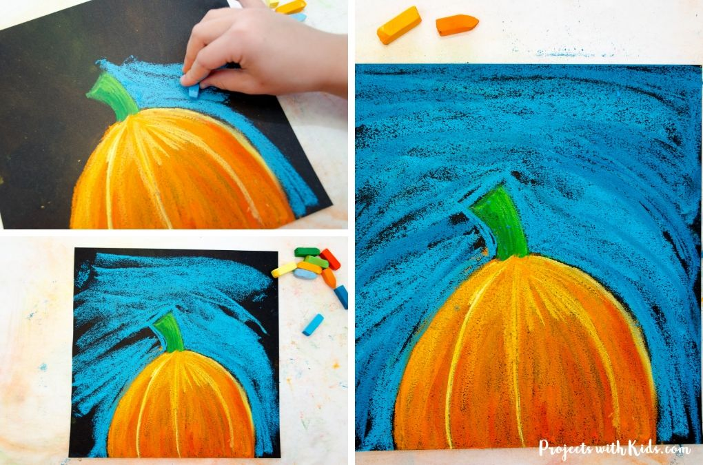 Using blue chalk pastel to color in a sky on black paper for an autumn chalk pastel art project.