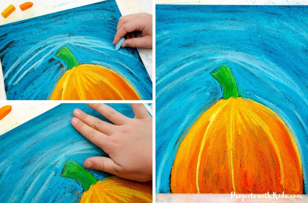 Finishing using blue chalk pastels to create a blue sky for a pumpkin chalk pastel art project.