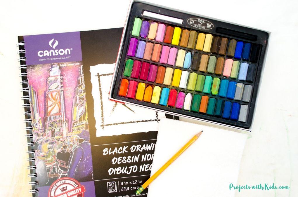Black drawing paper, chalk pastels, paper towels, pencil