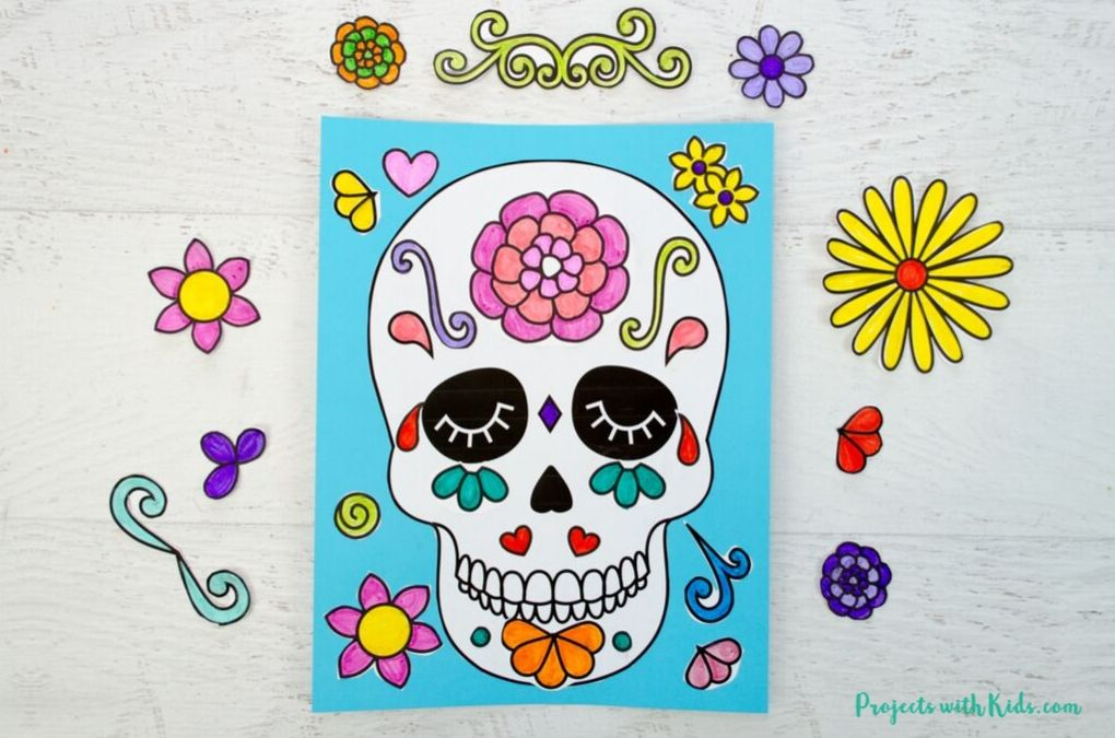 Finished image of a sugar skull art project glued onto blue paper.