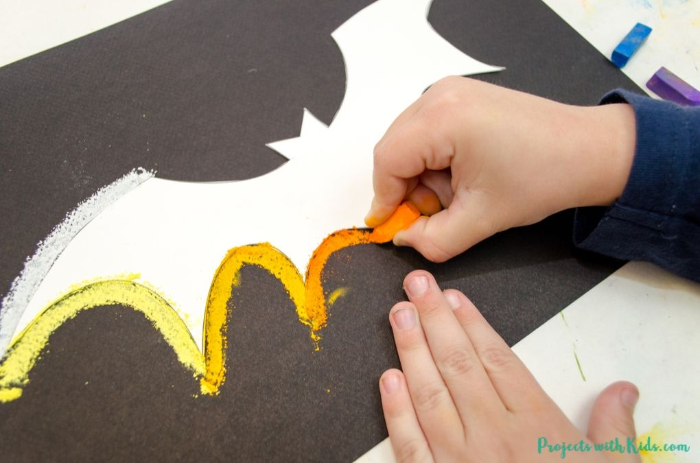 Drawing around a bat template with orange chalk pastel on black paper