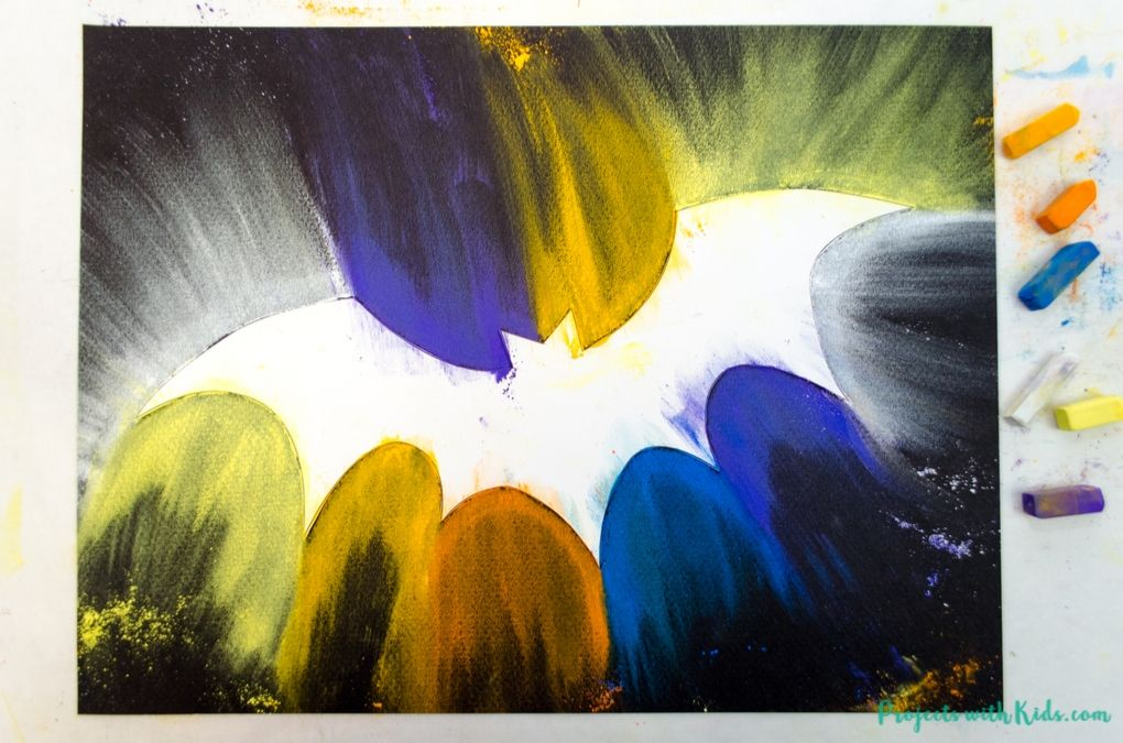 Colored chalk pastel smudged all the way around a bat template on black pastel paper