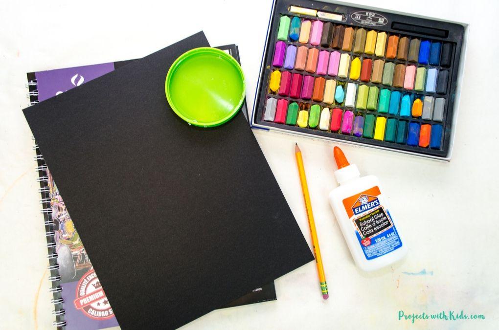 Black drawing paper, plastic lid, glue, pencil, chalk pastels
