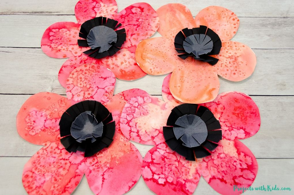 red watercolor poppy art with black and grey paper centers.